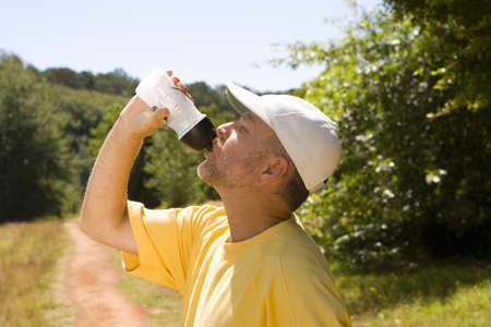 Man on country path drinking from water bottle, profile