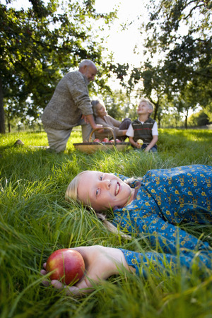 Portrait of girl (11-13) lying in grass with apple,parents and brother (9-11) in background