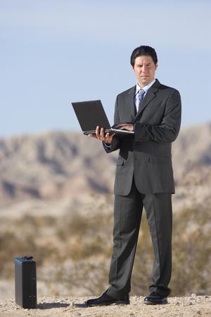 Businessman by briefcase using laptop computer in desert, portrait