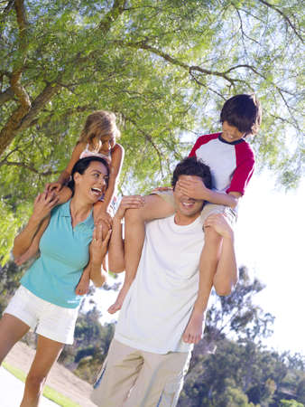 Family of four outdoors, children (4-8) on parents shoulders