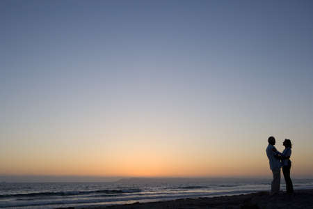 Silhouette of couple embracing on beach, dusk