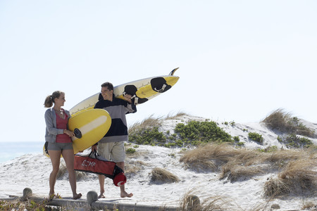 Young couple carrying yellow surfboards on beach, smiling LANG_EVOIMAGES