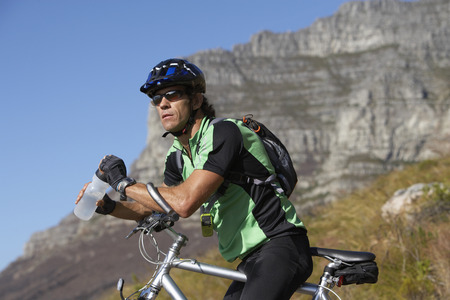 Male mountain biker sitting on bicycle, looking at view, side view