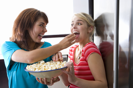Two young women eating popcorn, smiling