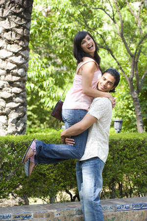 Young couple outdoors, man lifting up woman, portrait