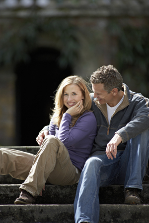 Couple sitting on steps, smiling
