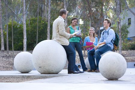 Teenage school students (16-18) in conversation with teacher outdoors, sitting on concrete balls