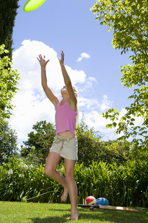 Girl (9-11) preparing to catch flying disc in garden, low angle view