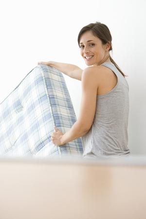 Woman moving mattress, smiling LANG_EVOIMAGES