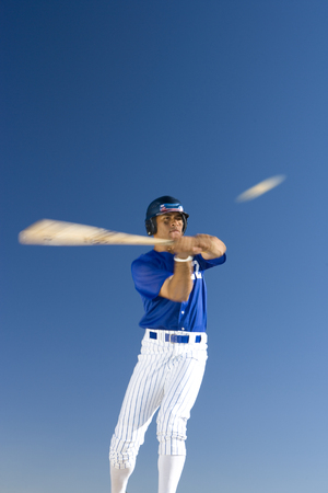 Baseball batter standing against clear blue sky, hitting ball, front view, low angle view (blurred motion)
