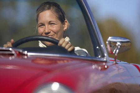 Woman driving red convertible car, smiling, front view, portrait
