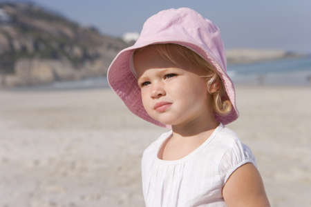 Baby girl (12-15 months) in hat on beach, close-up LANG_EVOIMAGES