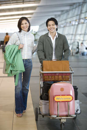 Couple pushing luggage trolley in airport, woman carrying green coat, smiling, front view, portrait LANG_EVOIMAGES