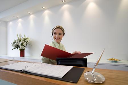 Receptionist at reception desk with folder, smiling