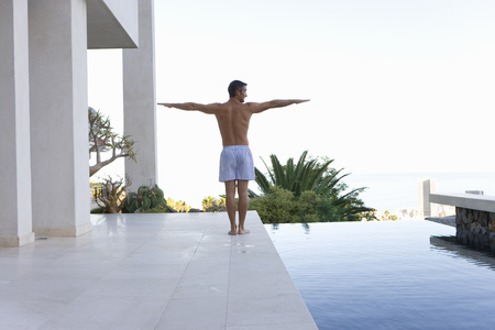 Young man stretching arms by swimming pool, rear view