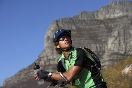 Male mountain biker sitting on bicycle, looking up, holding water bottle, side view