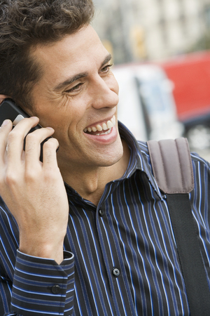 Man using mobile phone, smiling, close-up, outdoors