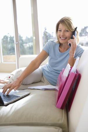 Mature woman sitting on sofa at home, using mobile phone and laptop, smiling, side view, portrait LANG_EVOIMAGES