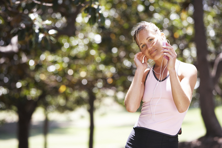 Woman listening to MP3 player in park, smiling, portrait LANG_EVOIMAGES