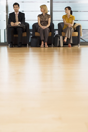 Businessman and two businesswomen sitting in office reception area, front view, surface level