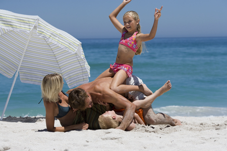 Father playfighting with two children (8-10) on sandy beach, woman looking on, smiling LANG_EVOIMAGES