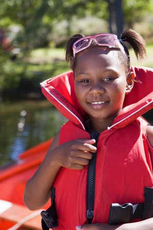 Girl (7-9) wearing red life jacket, smiling, close-up, portrait LANG_EVOIMAGES