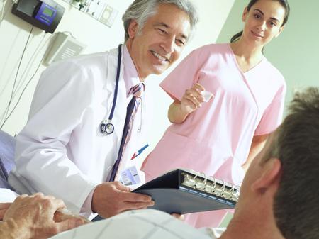 Doctor and nurse with patient, smiling (tilt) LANG_EVOIMAGES