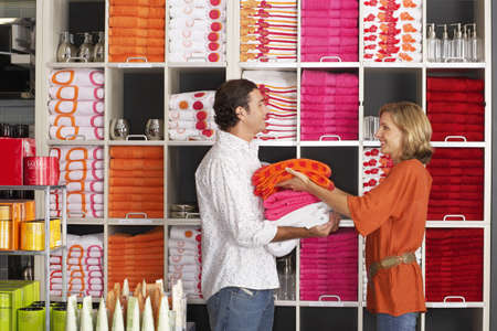 Couple shopping in department store, woman stacking multi-coloured towels in boyfriends arms, smiling, side view, shelves in background LANG_EVOIMAGES