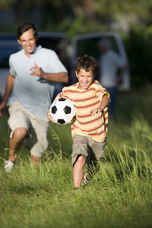 Father chasing son (8-10) across woodland clearing, boy carrying soccer ball underarm, smiling, front view