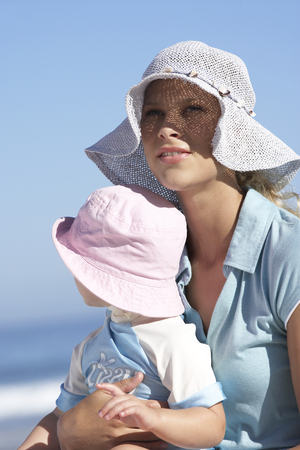 Mother and daughter (2-4) in sun hats sitting on beach, girl in womans lap, close-up