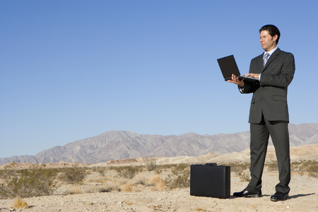 Businessman by briefcase using laptop computer in desert, low angle view LANG_EVOIMAGES