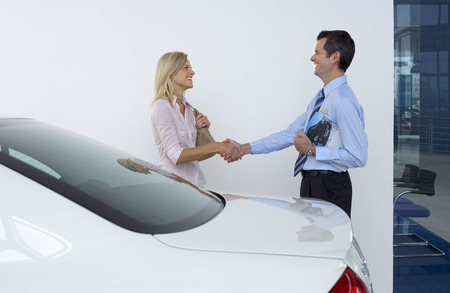 Car salesman shaking hands with female customer beside new car in showroom, man holding brochure, smiling, profile