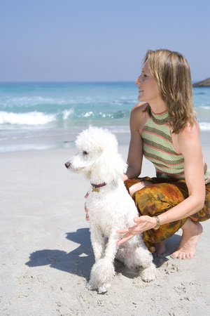 Woman with poodle on beach, looking out to sea