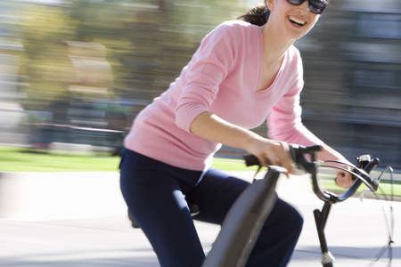 Businesswoman riding bicycle LANG_EVOIMAGES
