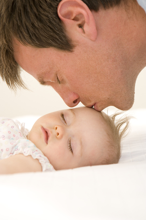 Father kissing baby girls (9-12 months) forehead, close-up, side view