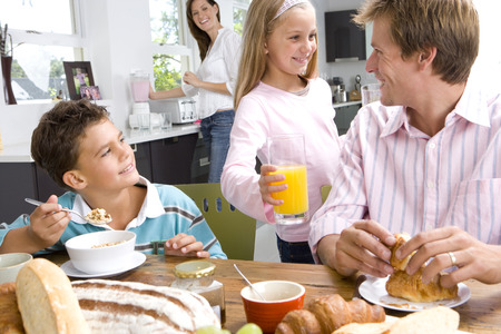 Family having breakfast at kitchen table, mother standing in background LANG_EVOIMAGES