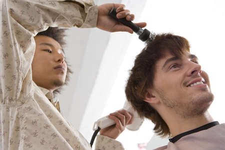 Hairdresser drying clients hair