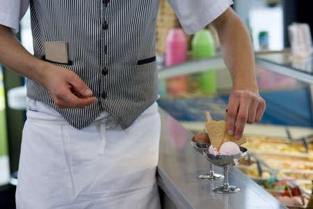 Waiter preparing ice cream dessert, mid section