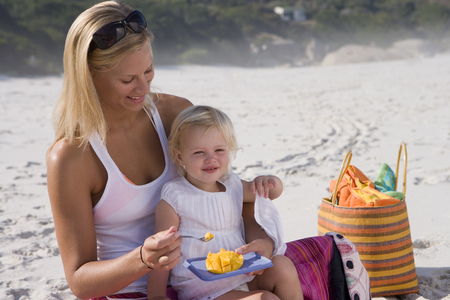 Mother feeding daughter (12-15 months) on beach, smiling