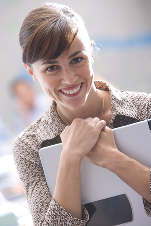 Businesswoman with laptop computer in office, smiling, portrait