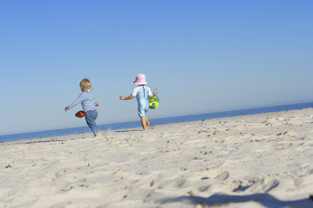 Two girls (2-5) running on sandy beach, rear view, surface level (tilt)