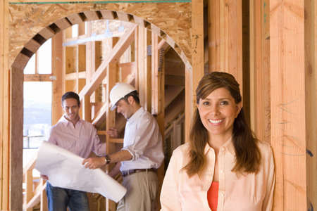 Portrait of woman smiling by architect showing blueprint to man in partially built house