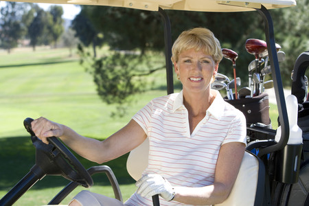 Mature woman, in striped polo shirt and golf glove, sitting in golf buggy on golf course, smiling, side view, portrait