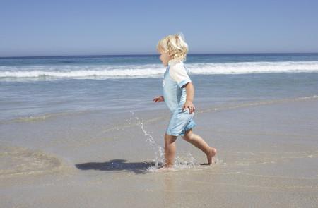 Blonde girl (2-4) walking ankle deep in water on sandy beach, smiling, profile