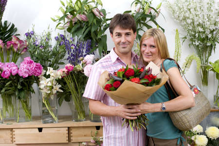 Couple with bouquet of flowers in shop, smiling, portrait LANG_EVOIMAGES
