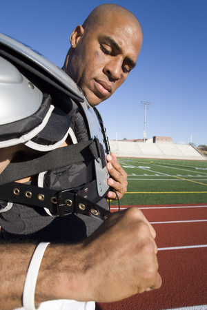 American football player adjusting protective shoulder pad strap pitchside on sports track, side view