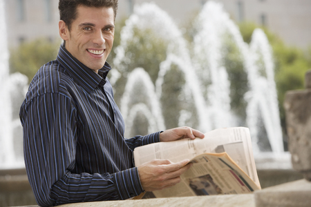 Man standing near fountain, holding financial newspaper, smiling, side view, portrait