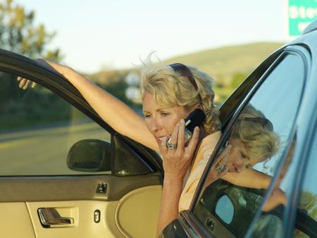 Mature woman on mobile phone in car, door open