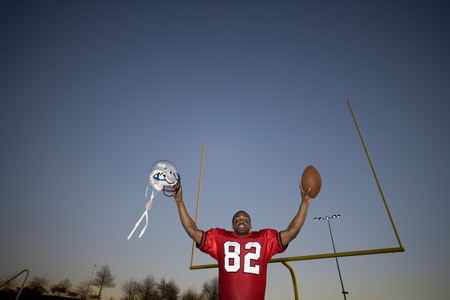 American football player, in red football strip, celebrating victory on pitch at sunset, arms up, holding ball and protective helmet in front of goal post, low angle view, portrait LANG_EVOIMAGES