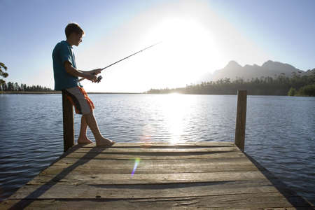Solitary teenage boy (12-14) standing at edge of jetty, fishing in lake on sunny day, side view (lens flare, backlit)